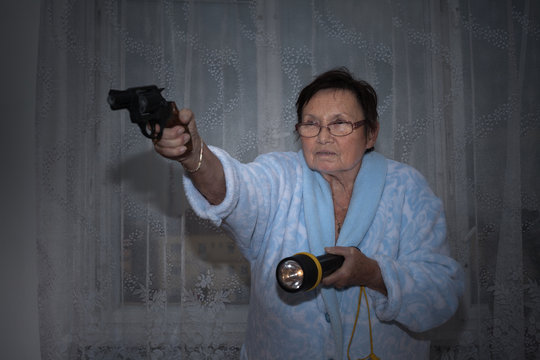 Senior woman with a gun and torch
