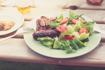 Meat and salad outdors on table