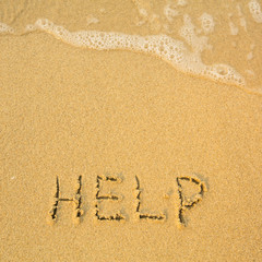 Help - written in sand on beach texture - soft wave of the sea.