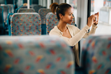 Young woman taking a photo on train with her phone
