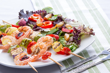 Gourmet shrimp skewers with salad greens