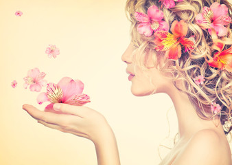 Girl takes beautiful flowers in her hands. Blowing flower