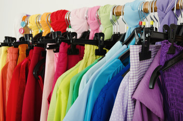 Close up on color coordinated clothes on hagers in a store.