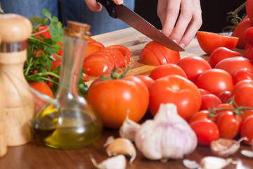 female hands  slicing tomatoes