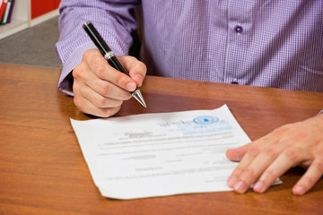 Close up of a male's hand, signing document.