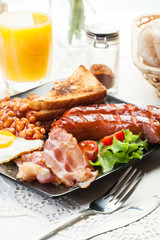 Full English breakfast with bacon, sausage, egg, baked beans and