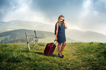 Woman on a mountain trail with a suitcase