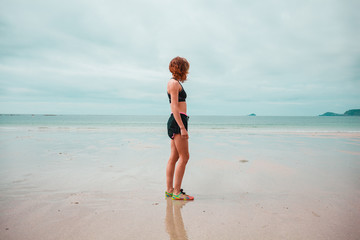 Young woman in workout clothes standing on beach