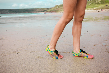 The legs of a young woman on the beach