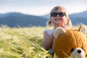 Girl and Teddy bear in a wheat field