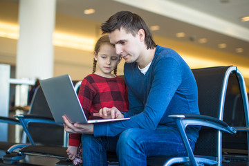 Father and little girl with laptop at the airport while waiting