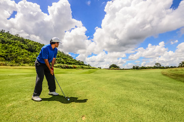 Golfer swinging his gear and hit the golf ball from tee to the f