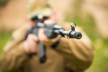 Man in camouflage with a shotgun aiming at a target. Focus on ho