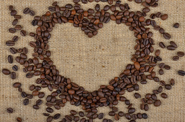 Heart from coffee beans on burlap background