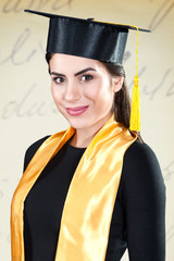 Young woman over isolated background dressed in graduation clothes.