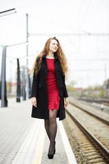 Woman at red dress on train platform