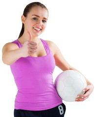 Fit brunette holding ball showing thumbs up