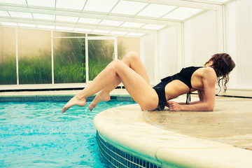 Sexy young woman posing by swimming pool
