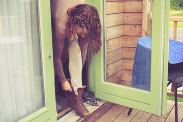 Woman tying her boots in holiday cabin