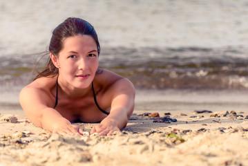 Schöne junge Frau liegt im Sand am Strand