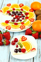 Homemade sweet pizza with fruits on wooden table, close up
