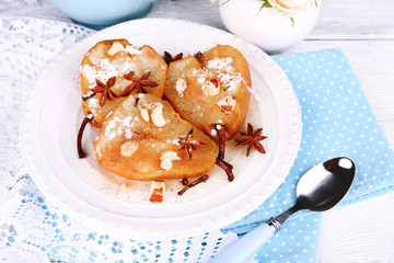 Baked pears with syrup on plate, on bright background