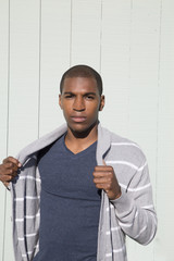 Attractive black male model holding his striped sweater
