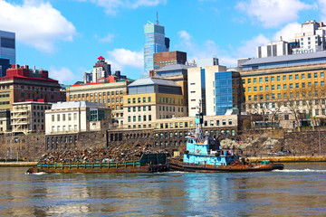 Daily trash removal by large barges in New York.
