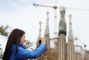 Woman with digital camera photographing  Sagrada Familia