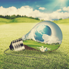Eco energy concept. Light bulb with green world inside over natu