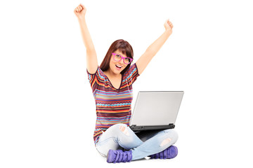 Woman working on laptop and gesturing success