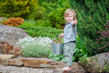 Happy child with thumbs-up in the beautiful spring garden