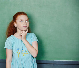 Mädchen an Tafel beim Nachdenken