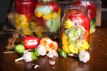 preserved cucumbers, peppers and patisson in jars