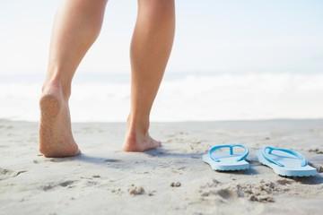 Female feet stepping on sand beside flip flops