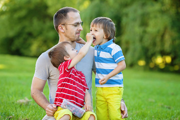 Father with two kids, eating cherries