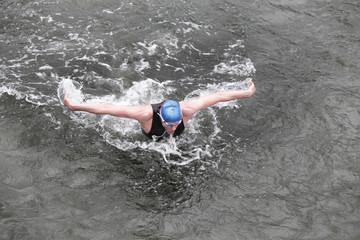 swimmer in wetsuit performing the butterfly stroke in ocean
