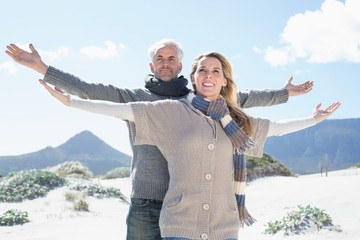 Carefree couple standing on the beach in warm clothing
