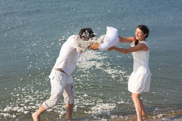 Young couple fighting pillows on the beach