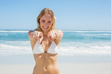 Beautiful blonde smiling at camera on the beach