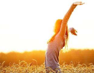 Young woman enjoying sunlight with raised arms in straw field