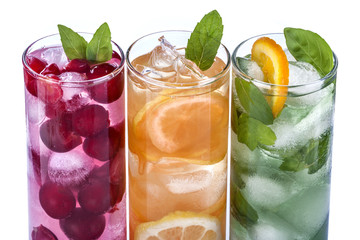 iced drinks with cherry, orange and mint on white background