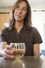 Attractive Middle Aged Woman in the Kitchen Drinking Wine