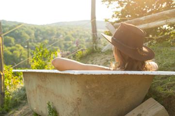Sexy cowgirl sitting in bath on ranch