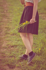 Background girl walking in a field in a dress and sneakers