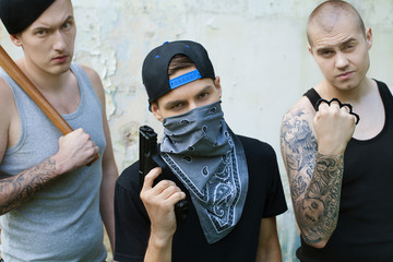 three gangsters with weapons looking into camera.