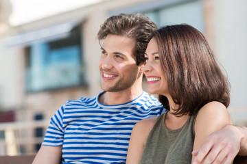 glückliches paar sitzt auf einer bank an der straße