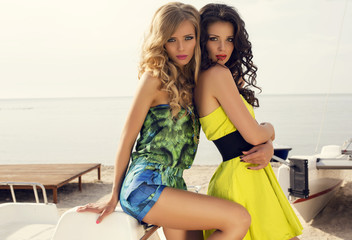 fashion photo of two beautiful girls in colorful dresses
