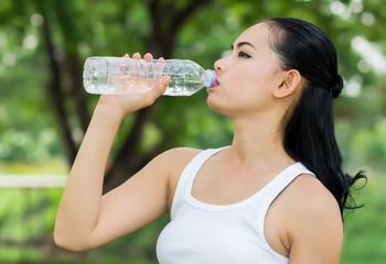 Young beautiful dark-haired woman wearing t-shirt drinking water