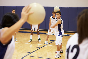 High School Students Playing Dodge Ball In Gym